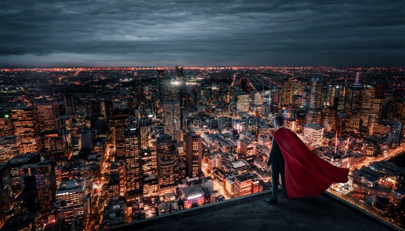 Hombre de negocios con el cabo rojo que se coloca en el tejado foto de archivo libre de regalías