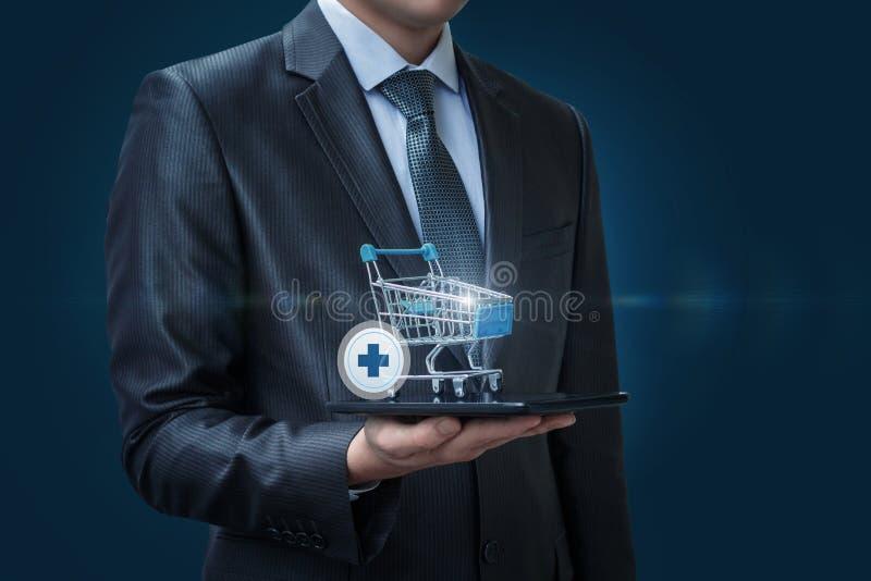 Hombre de negocios con el carro de la compra y el icono para añadir una compra foto de archivo