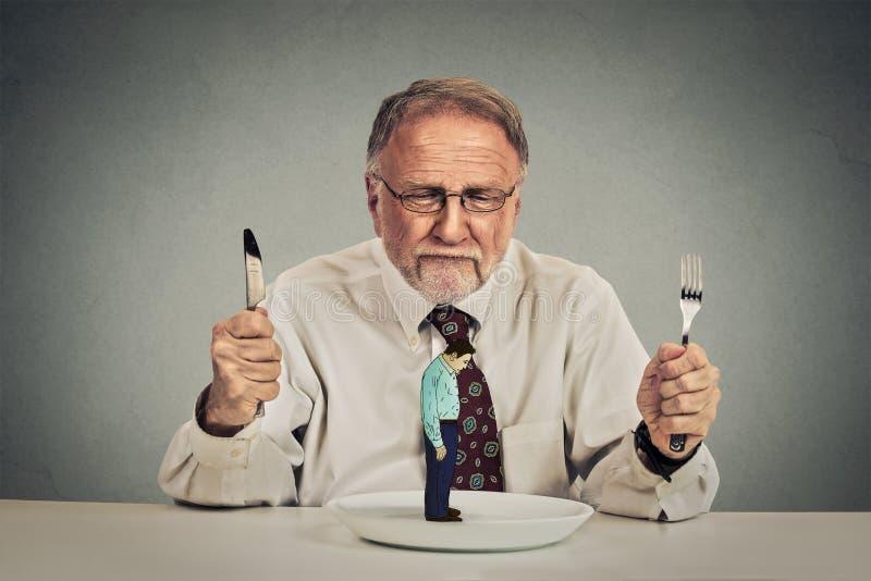 Hombre de negocios con el cuchillo y bifurcación que mira a su empleado en una placa foto de archivo libre de regalías