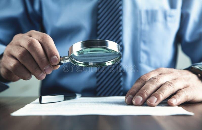 Hombre de negocios con el documento de la lectura de la lupa imagen de archivo