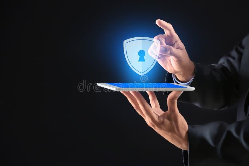 Hombre de negocios con el icono de la tableta y del escudo en fondo oscuro Concepto de la seguridad de datos imagen de archivo libre de regalías