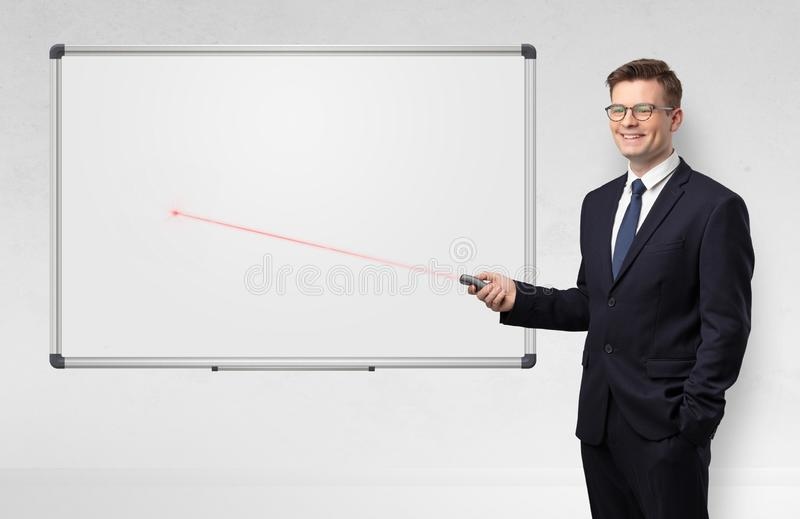Hombre de negocios con el indicador del laser y la pizarra del blanco del copyspace foto de archivo