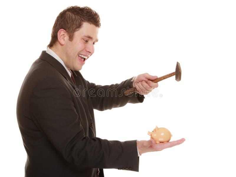 Hombre de negocios con el martillo alrededor para romper la hucha imagen de archivo
