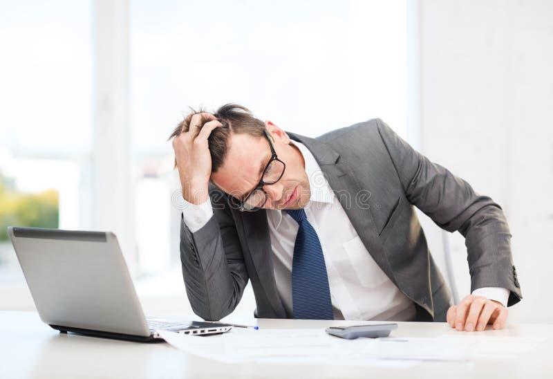 Hombre de negocios con el ordenador, los papeles y la calculadora fotografía de archivo libre de regalías