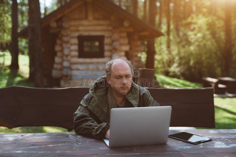 Hombre de negocios con el ordenador portátil durante sus vacaciones cerca de su hou del verano fotos de archivo libres de regalías