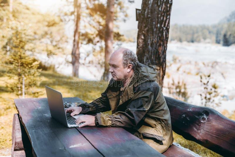 Hombre de negocios con el ordenador portátil durante sus vacaciones en bosque imagen de archivo libre de regalías