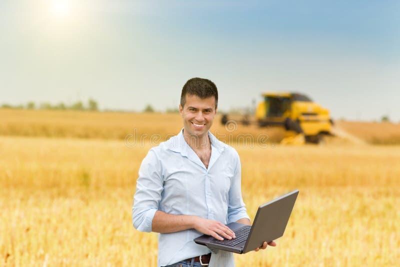 Hombre de negocios con el ordenador portátil en campo imagen de archivo libre de regalías