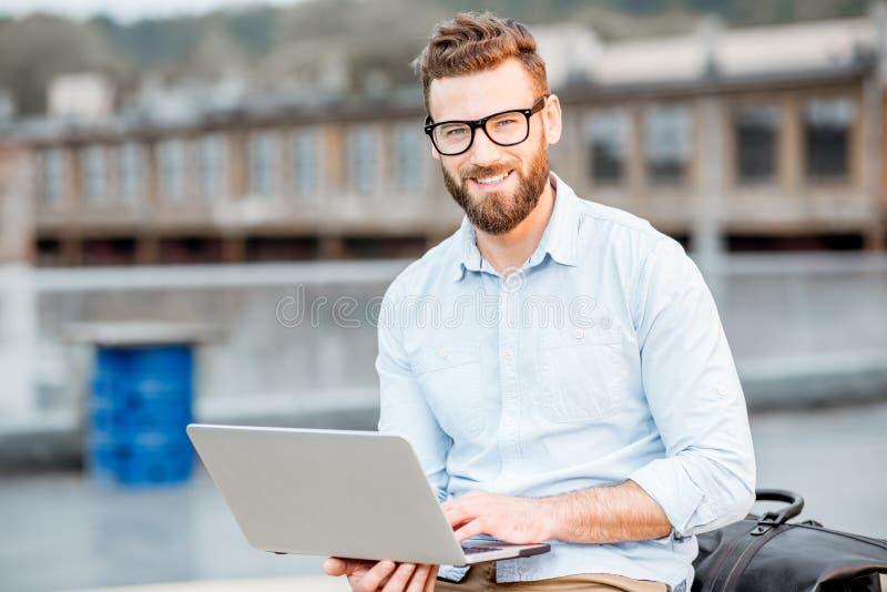 Hombre de negocios con el ordenador portátil en el tejado imagen de archivo