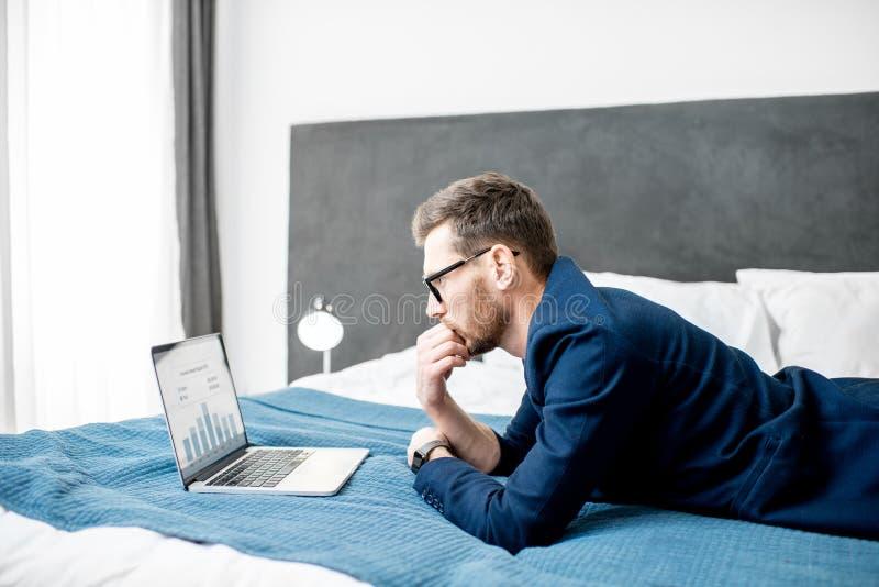Hombre de negocios con el ordenador portátil en la cama imagen de archivo