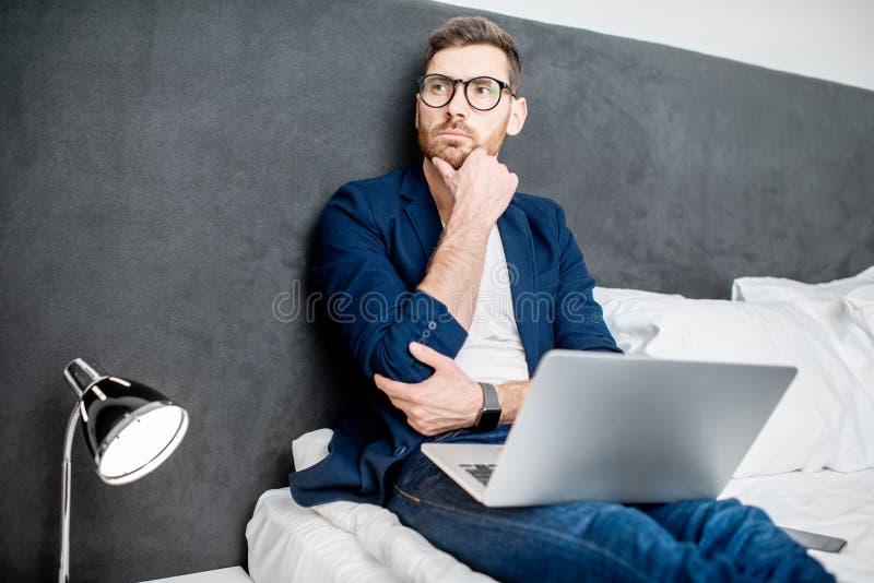 Hombre de negocios con el ordenador portátil en la cama imagen de archivo libre de regalías