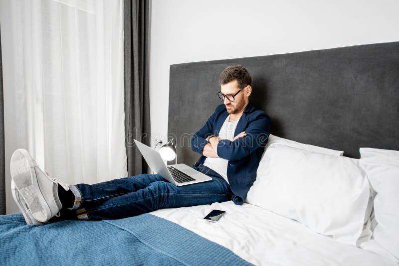 Hombre de negocios con el ordenador portátil en la cama imagenes de archivo