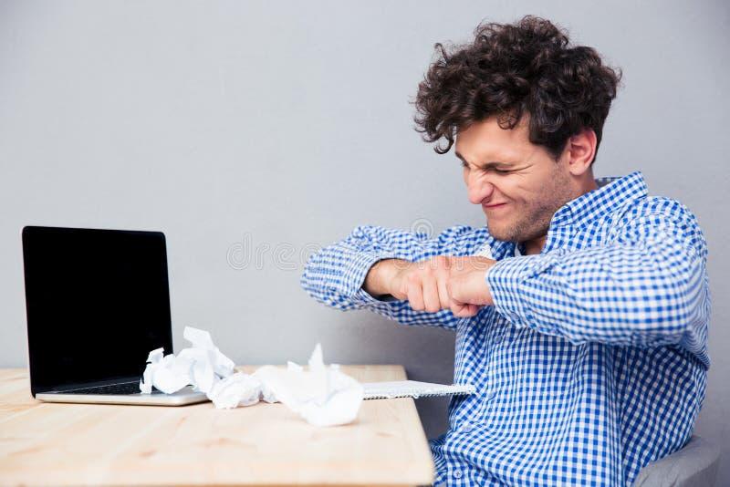 Hombre de negocios con el ordenador portátil y los papeles arrugados fotografía de archivo