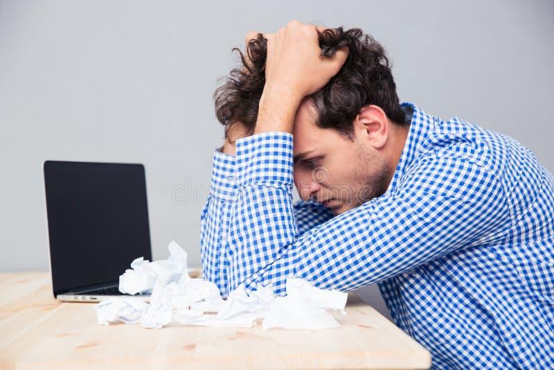 Hombre de negocios con el ordenador portátil y los papeles arrugados imagen de archivo