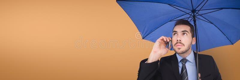 Hombre de negocios con el paraguas azul que habla en el teléfono contra fondo anaranjado imagen de archivo libre de regalías
