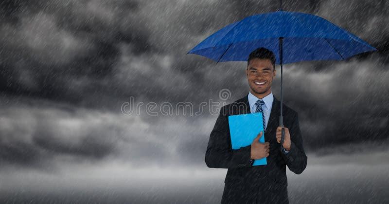 Hombre de negocios con el paraguas y el libro azul contra las nubes de tormenta con lluvia fotografía de archivo libre de regalías