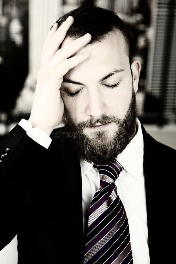 Hombre de negocios con el sufrimiento fuerte del dolor de cabeza imagenes de archivo