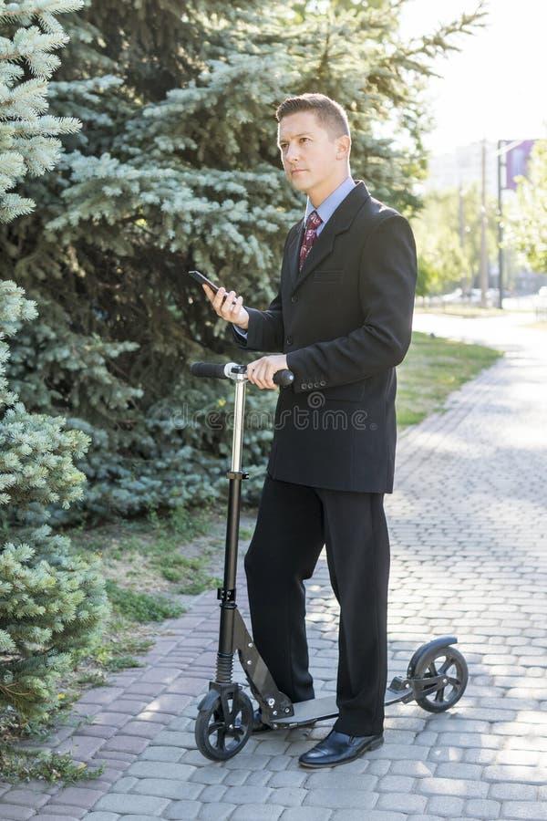 Hombre de negocios con el teléfono en la vespa fotografía de archivo libre de regalías
