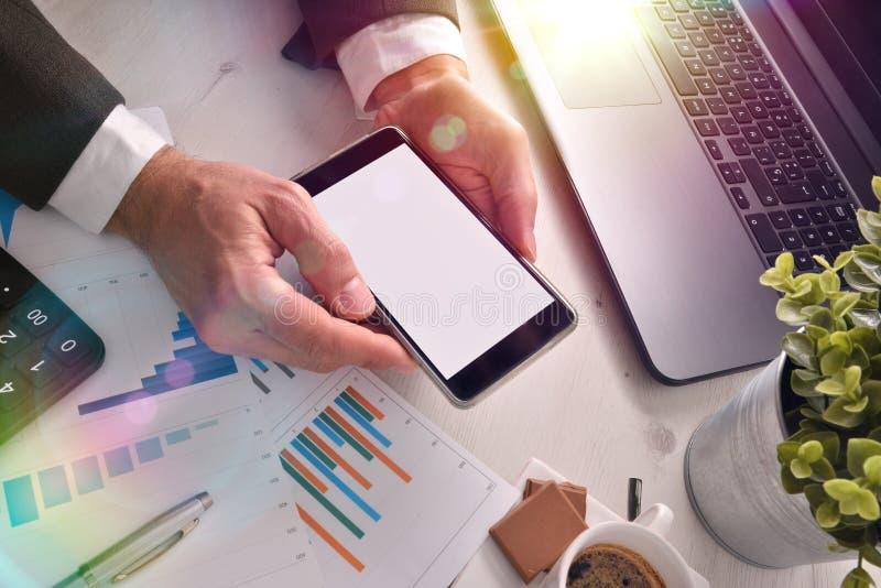 Hombre de negocios con el teléfono en su mano en una oficina foto de archivo libre de regalías