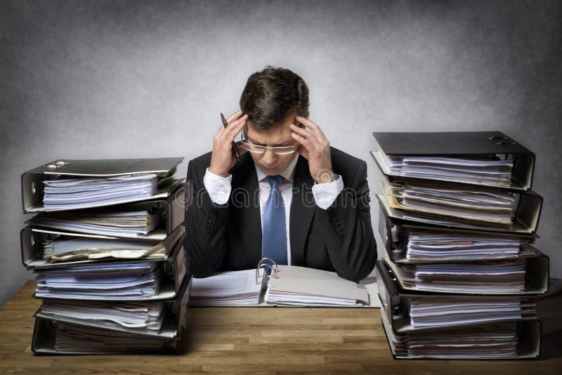 Hombre de negocios con exceso de trabajo imagen de archivo