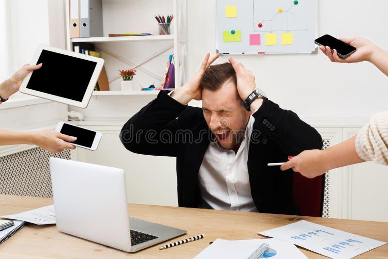 Hombre de negocios con exceso de trabajo subrayado jóvenes en oficina moderna fotografía de archivo