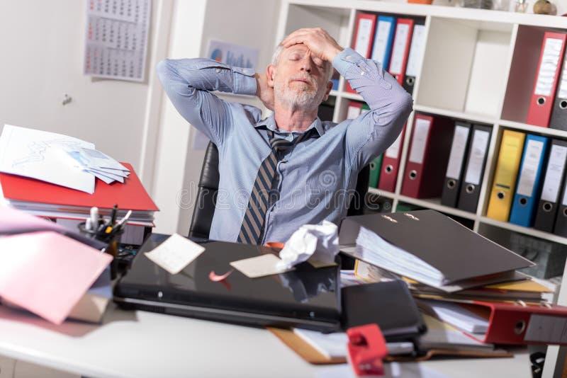 Hombre de negocios con exceso de trabajo que se sienta en un escritorio sucio imagen de archivo