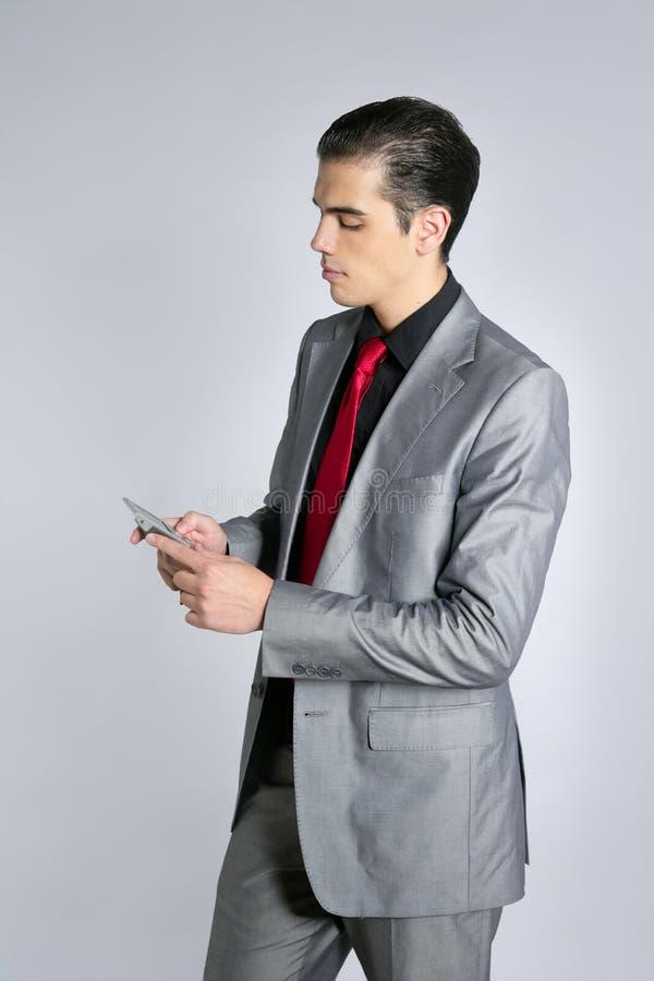 Hombre de negocios con hablar gris del juego celular fotos de archivo libres de regalías