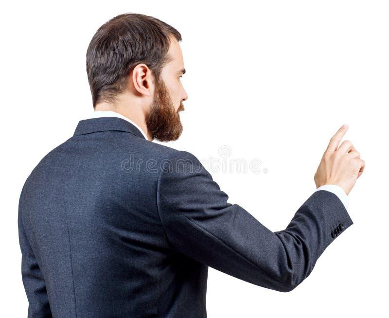 Hombre de negocios con la barba que se?ala algo o que toca por el ?ndice fotografía de archivo