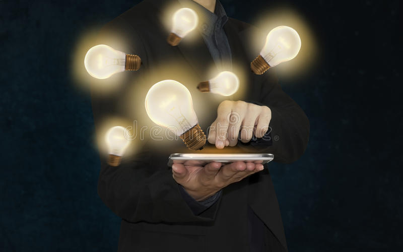 Hombre de negocios con la bombilla en la inspiración o la idea del concepto de la tableta, imagen de archivo libre de regalías