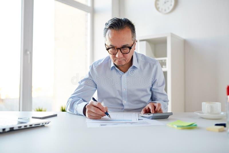 Hombre de negocios con la calculadora y los papeles en la oficina imagenes de archivo