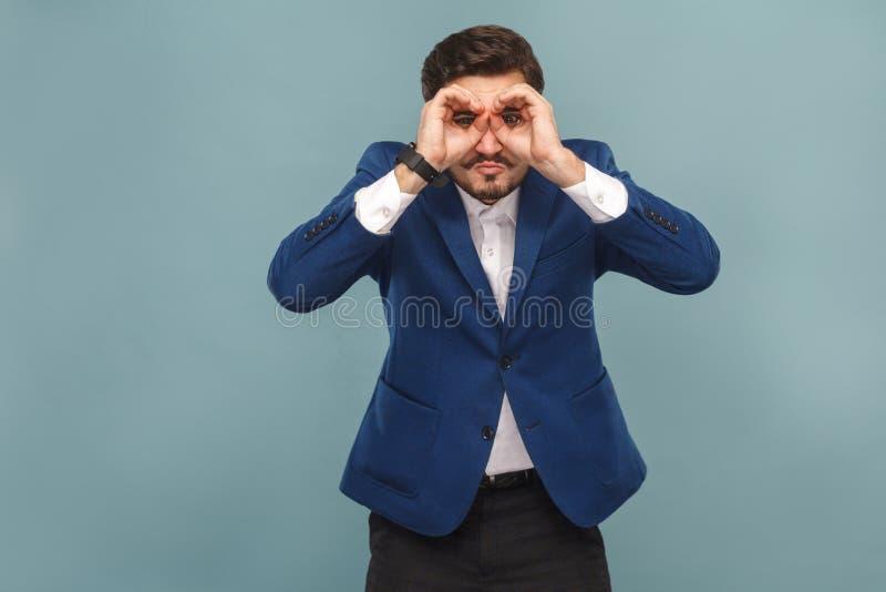 Hombre de negocios con la cara divertida que mira lejos en prismáticos fotos de archivo libres de regalías