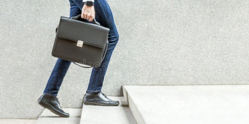 Hombre de negocios con la cartera negra a disposición que camina para arriba en las escaleras foto de archivo libre de regalías