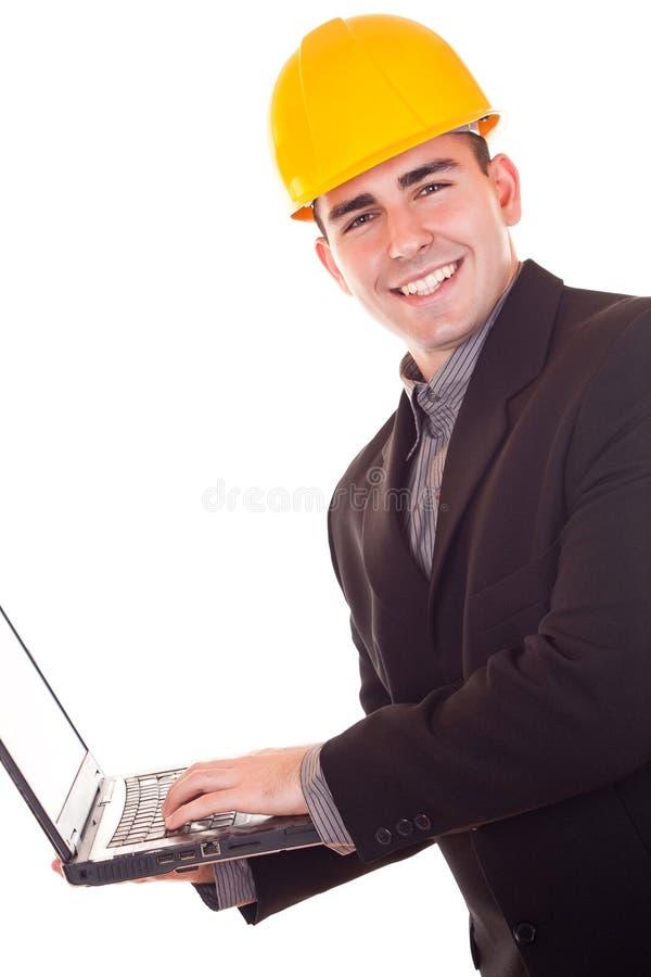 Hombre de negocios con la computadora portátil de la explotación agrícola del casco fotos de archivo