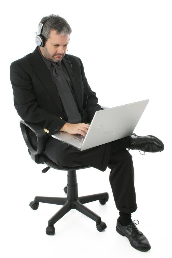 Hombre de negocios con la computadora portátil y los auriculares imagen de archivo