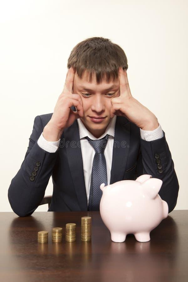 Hombre de negocios con la hucha rosada imagen de archivo