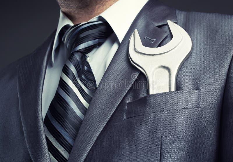 Hombre de negocios con la llave inglesa imagenes de archivo