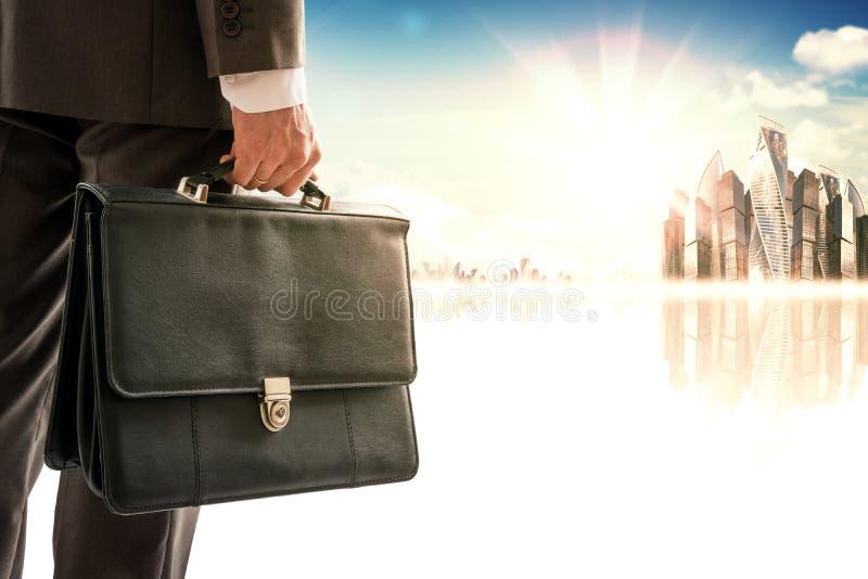 Hombre de negocios con la maleta contra ciudad moderna imágenes de archivo libres de regalías