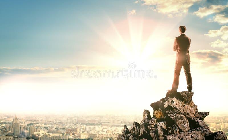 Hombre de negocios con la maleta que mira puesta del sol fotos de archivo