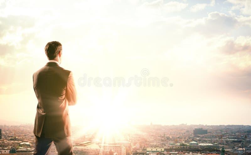Hombre de negocios con la maleta que mira puesta del sol imagen de archivo libre de regalías