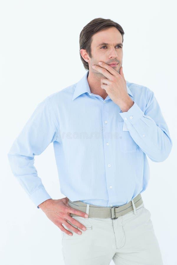 Hombre de negocios con la mano en la barbilla que mira lejos imagen de archivo libre de regalías