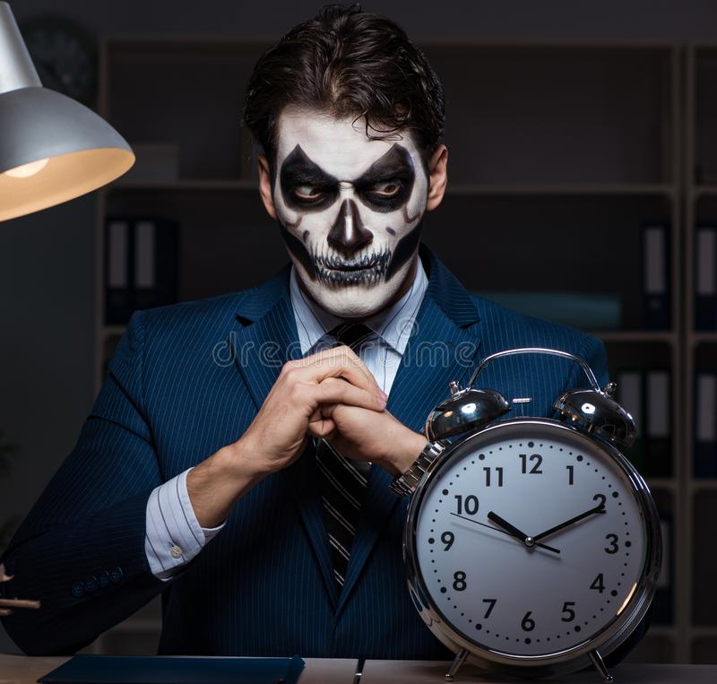 Hombre de negocios con la mascarilla asustadiza que trabaja tarde en oficina imagen de archivo libre de regalías