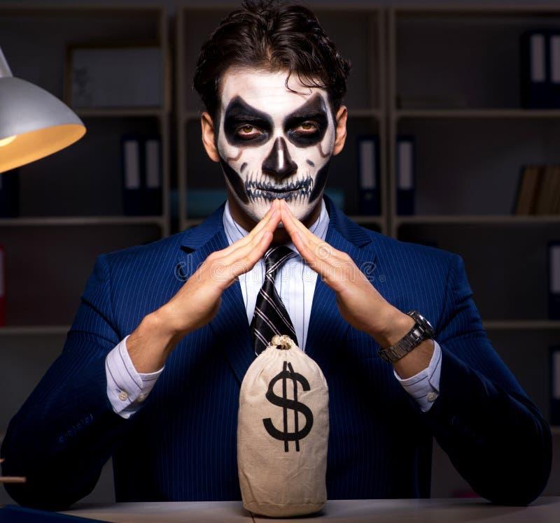 Hombre de negocios con la mascarilla asustadiza que trabaja tarde en oficina imagen de archivo