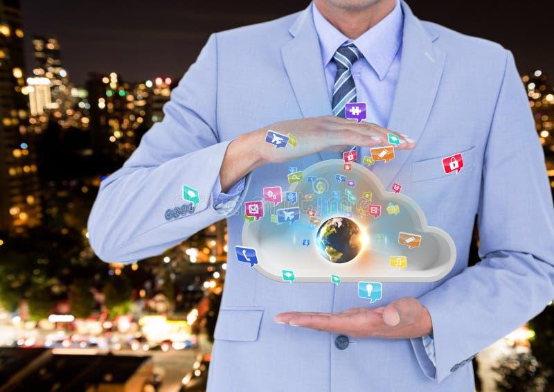 hombre de negocios con la nube entre sus manos y tierra en la nube e iconos de los usos que suben de ella imagen de archivo libre de regalías