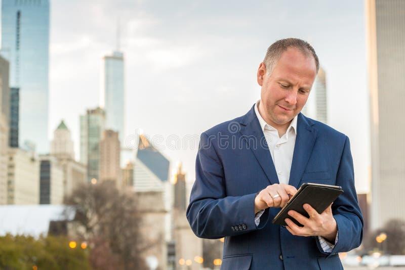 Hombre de negocios con la tableta delante de los edificios de oficinas fotografía de archivo libre de regalías