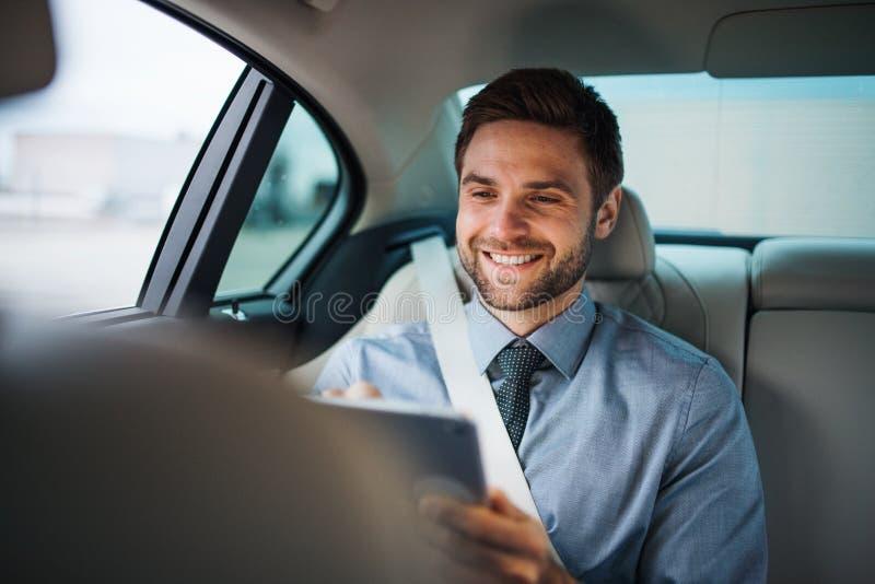 Hombre de negocios con la tableta que se sienta en asientos traseros en el coche, trabajando foto de archivo libre de regalías