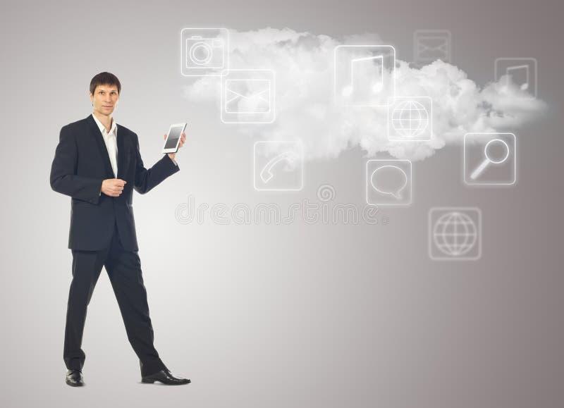 Hombre de negocios con la tableta y la nube con los iconos de los usos encendido imagenes de archivo