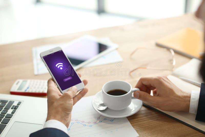 Hombre de negocios con la taza de café y de teléfono móvil usando Wi-Fi libre en el lugar de trabajo foto de archivo libre de regalías