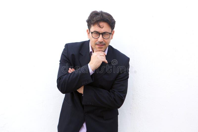 Hombre de negocios con las gafas que se oponen con la mano en la barbilla al fondo blanco fotos de archivo libres de regalías