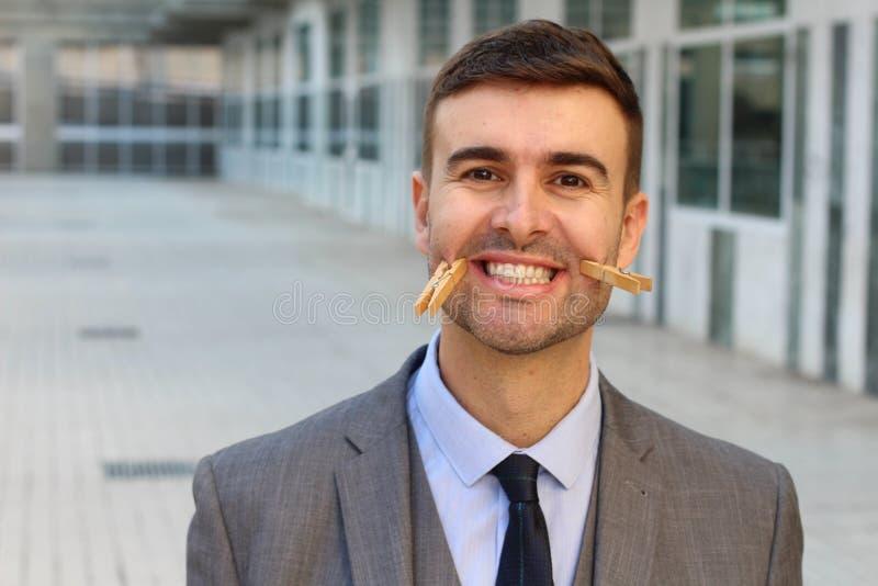 Hombre de negocios con las pinzas que crean una sonrisa falsa imagen de archivo libre de regalías