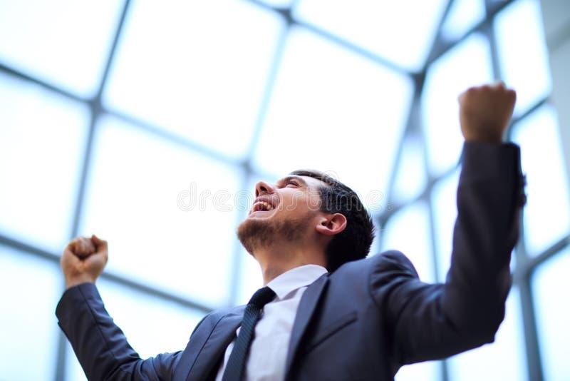 hombre de negocios con los brazos para arriba que celebra su victoria foto de archivo