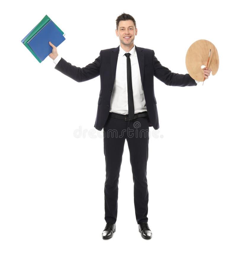 Hombre de negocios con los cuadernos y la paleta de la pintura imagen de archivo